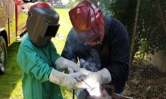 Bridgemania student welding outdoors with supervision.