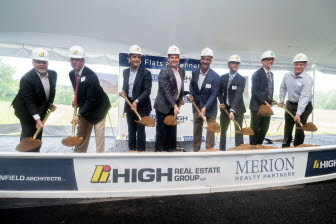 A group of executives celebrates a groundbreaking by scooping a shovelful of earth.