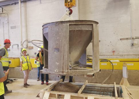 A high school teacher pours concrete into a mold with High Concrete Group co-workers.