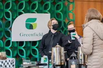 Two masked women serve coffee to a third woman in front of a Greenfield backdrop.