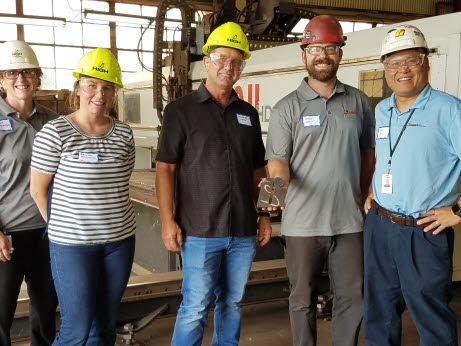 Teachers pause while touring High Steel Structures LLC with High co-workers.