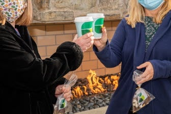 Two masked women clink hot chocolate cups in front of a fireplace.