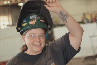 A young woman in an open welding helmet smiles at the camera.